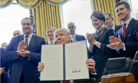 Trump holds up his executive order creating regulatory reform task forces.