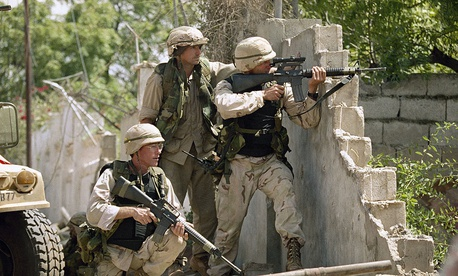 United States soldiers return fire at snipers from behind a wall just outside the compound of Somali warlord Mohamed Farrah Aidid in Mogadishu in 1993.