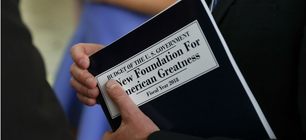 """White House budget director Mick Mulvaney, holds a copy of """"Budget of the U.S. Government A New Foundation For American Greatness Fiscal Year 2018."""""""