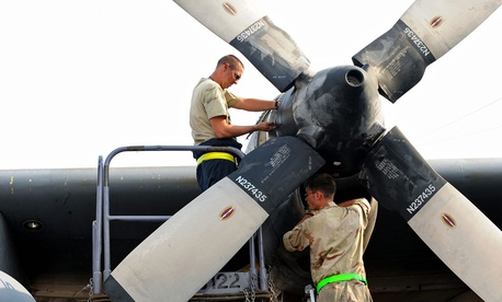 U.S. Air Force Tech. Sgt. Christopher Chadwell, left, performs a propeller hydraulic fluid level check while Staff Sgt. William Aker does an engine inlet inspection on a C-130E Hercules aircraft somewhere in southwest Asia in 2010.