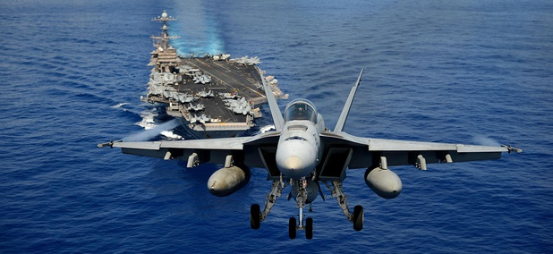 An F/A-18E Super Hornet from the Tophatters of Strike Fighter Squadron (VFA) 14 participates in an air power demonstration over the aircraft carrier USS John C. Stennis (CVN 74).