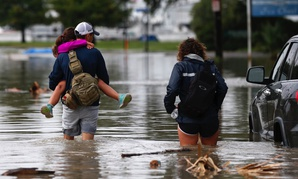 Don Noel carries his daughter Alexis, 8, with his wife Lauren, right as they walk through a flooded roadway to check on their boat in the West End section of New Orleans on Wednesday.