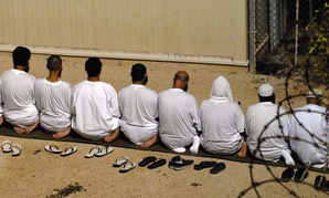 A group of detainees kneel as they observe morning prayer before sunrise inside Camp Delta in 2009.