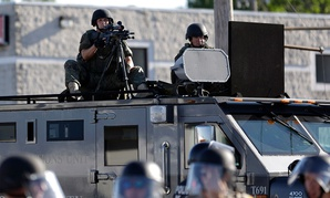 A police tactical team moves in to disperse a group of protesters following the shooting of a young black man by a white policeman in Ferguson, Mo., in 2014.
