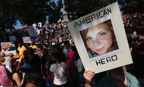 """A counter-protester holds a photo of Heather Heyer on Boston Common at a """"Free Speech"""" rally organized by conservative activists Saturday in Boston."""