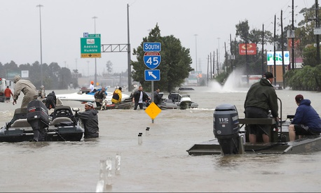 Volunteer rescue boats make their way into a flooded subdivision to rescue stranded residents as floodwaters rise in Spring, Texas on Monday.
