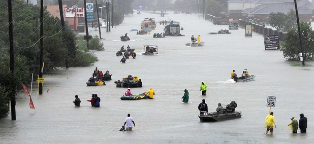 Rescue boats fill a flooded street at flood victims are evacuated as floodwaters from Tropical Storm Harvey rise Monday.