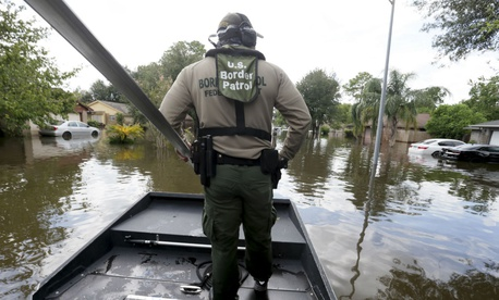 U.S. Border Patrol Agent Steven Blackburn looks out while standing on the bow of an air boat during a search a rescue operation in Houston.