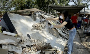 Lucy Liu dumps trash on a pile of debris as she helps her co-worker Tianna Oliver clean out her flood-damaged house Aug. 31 in Houston.