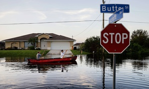 Pierre Ghantos, left, and his son Nathan paddle though their flooded neighborhood in the aftermath of Hurricane Irma in Fort Myers on Tuesday.