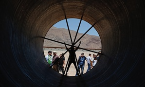 People stand in a metal tube after a test of a Hyperloop One propulsion system in May 2016 in North Las Vegas, Nevada.
