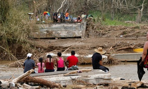 People sit on both sides of a destroyed bridge that crossed over the San Lorenzo de Morovis river, in the aftermath of Hurricane Maria, in Morovis, Puerto Rico.