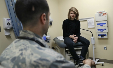 Dr. David Klein, an Air Force Major and chief of adolescent medicine at Fort Belvoir Community Hospital, left, speaks with Jenn Brewer, 13, during an appointment in September 2016.