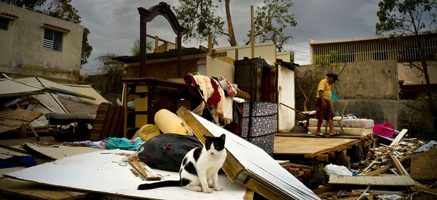 Efrain Diaz Figueroa walks by his sister's home destroyed in the passing of Hurricane Maria in San Juan on Monday.