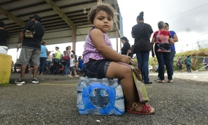 Kerialys Aldea de Jesus sits on bottled water at the Jose de Diego Elementary School where residents file FEMA forms for federal aid in the aftermath of Hurricane Maria in Puerto Rico Oct. 2.