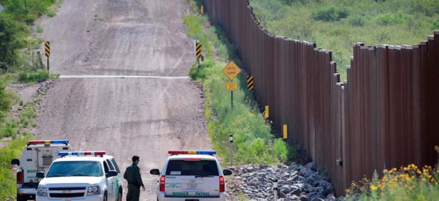Agents confer near the border in Naco, Ariz.