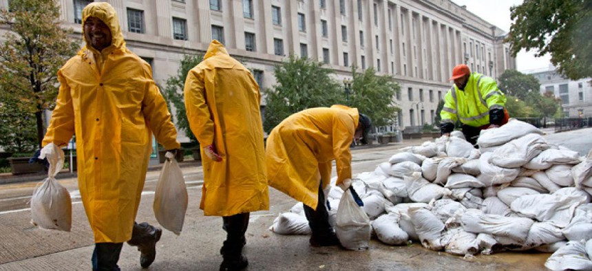 Workers hauled sandbags in front of the Justice Department to prepare for Sandy in October.  The department closed for two days during the storm.