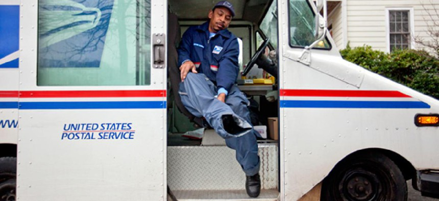 U.S. Postal Service letter carrier of 19 years, Michael McDonald, puts on his rain pants before delivering mail.