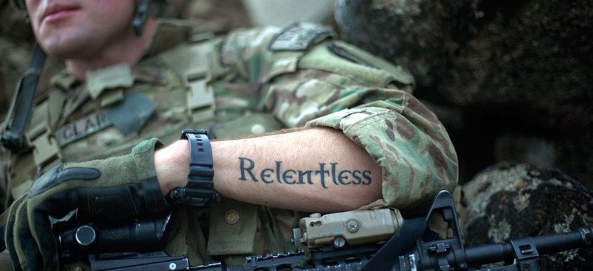 """A tattoo reading """"relentless"""" decorates the arm of U.S. Army Pfc. Mitchell Clark in in Kunar province, Afghanistan."""