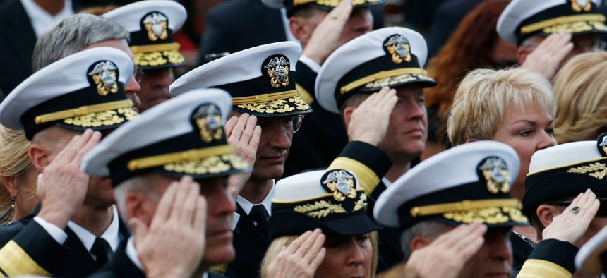 """Navy personnel salute during the playing of """"Taps"""" at a memorial service for the victims of the Washington Navy Yard shooting."""