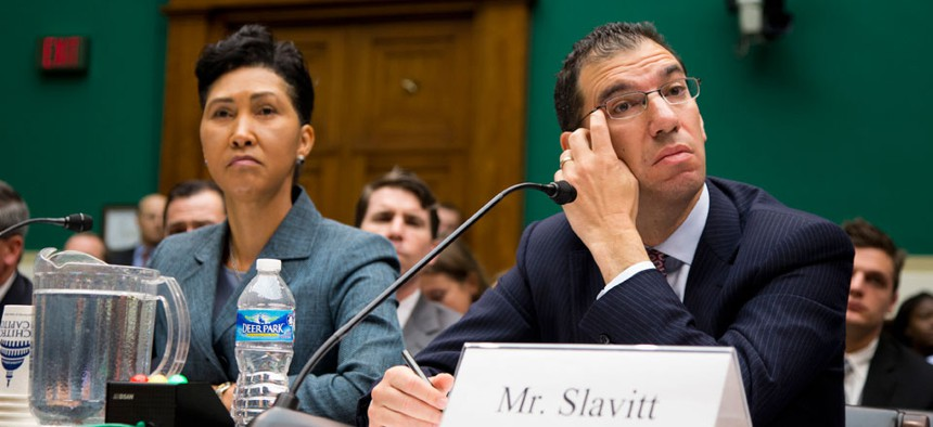 Cheryl Campbell, senior vice president of CGI listens at left as Andy Slavitt, representing QSSI's parent company, testified on Oct. 24