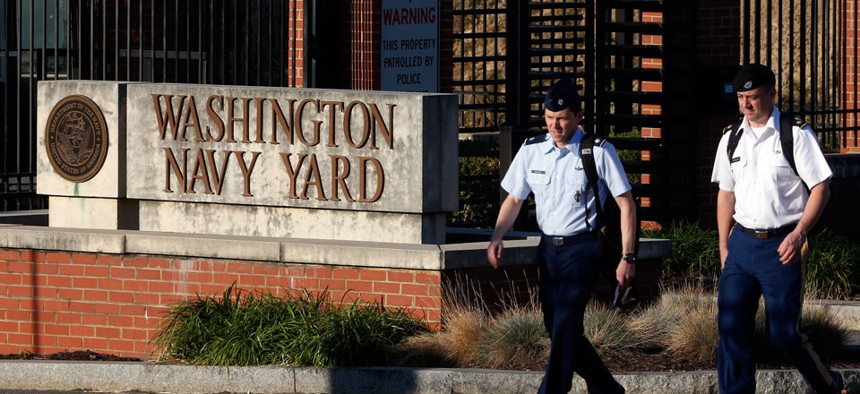 Military personnel walk past an entrance to the Washington Navy Yard Thursday, Sept. 19, 2013.