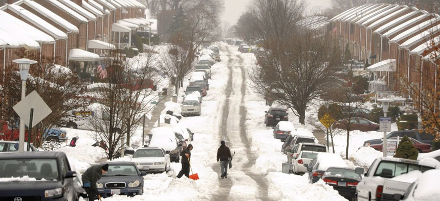 People clear snow after a storm in Baltimore Thursday, Feb. 13, 2014.