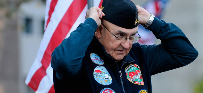 Submarine veteran Lawrence Check adjusts his hat before watching a parade on Veterans Day in Atlanta in 2012.
