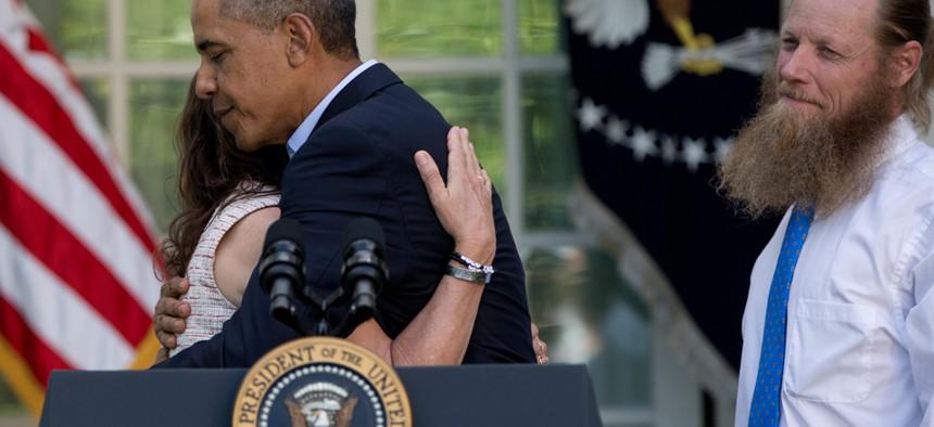 Obama hugs Jani Bergdahl, as Bob Bergdahl stands nearby on May 31.
