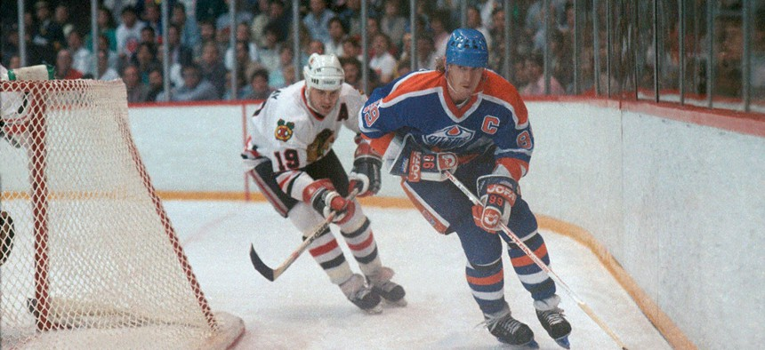 Wayne Gretzky advances the puck against the Chicago Blackhawks' Troy Murray in 1987 at Chicago Stadium.