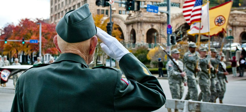 Retired Army 1st Sgt. William Staude, of Elliott, Pa., salutes the colors being carried by soldiers from the 316th Expeditionary Sustainment Command.