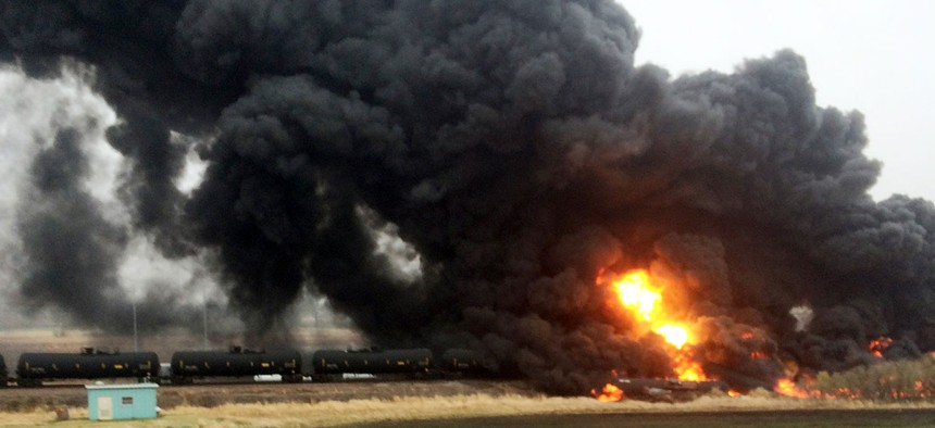 A train spews smoke and fire after it derailed, May 6, in Heimdal, N.D.