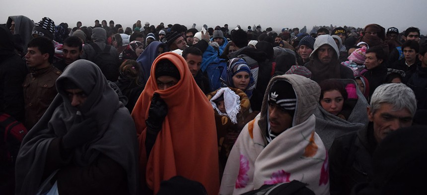 Refugees wait to be allowed to cross from the northern Greek village of Idomeni to southern Macedonia Friday.