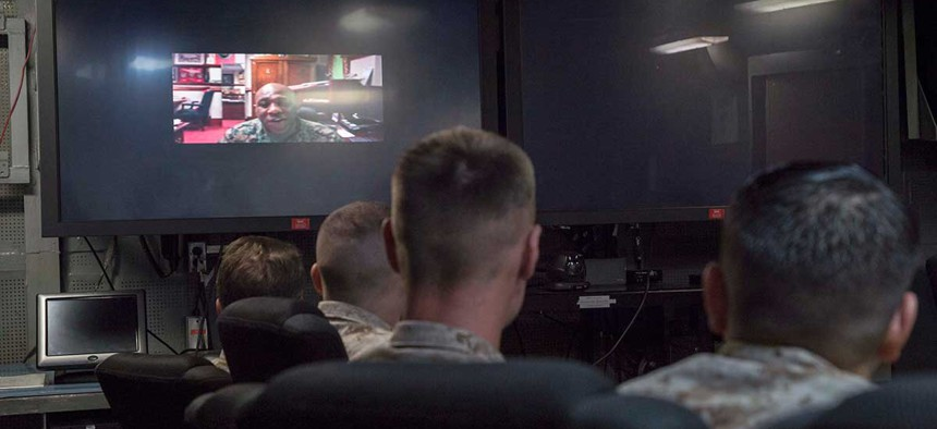 The 18th Sgt. Maj. of the Marine Corps, Ronald Green, speaks to Marines and Sailors attached to the 26th Marine Expeditionary Unit (MEU) in the flag plot conference room during a video teleconference call in February