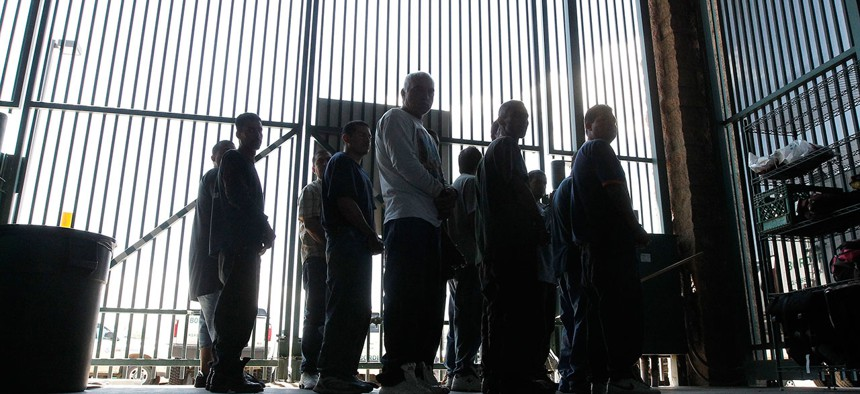 People are transferred out of the holding area after being processed at the Tucson Sector of the U.S. Customs and Border Protection headquarters in Tucson, Ariz. in 2012.