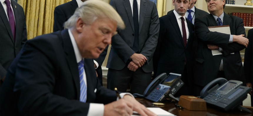 President Trump signs executive orders in the Oval Office on Monday.