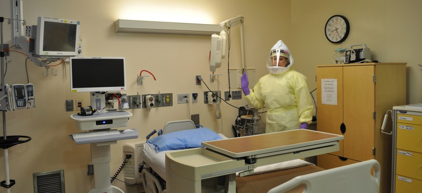 A NIH Clinical Center Special Clinical Sudies Unit nurse stands in one of the unit's patient care rooms.