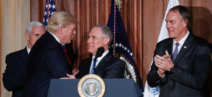 President Donald Trump shakes hands with Environmental Protection Agency Administrator Scott Pruitt, flanked by Vice President Mike Pence and Interior Secretary Ryan Zinke in March.
