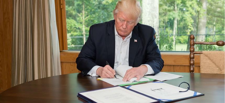 President Donald Trump signs the Hurricane Harvey Funding Bill.