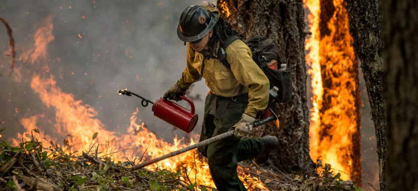"""A member of an interagency firefighting crew conducts a prescribed burn """"burnout"""" operation in Oregon to help stop the main fire from spreading."""