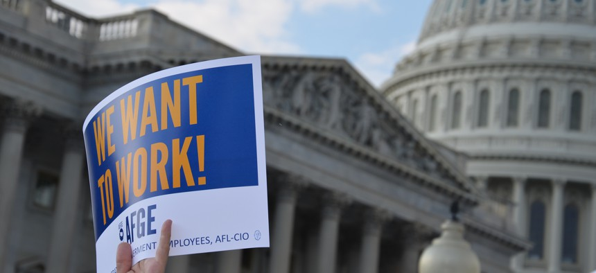 An AFGE member holds a sign during a rally in D.C. during the 2013 shutdown.