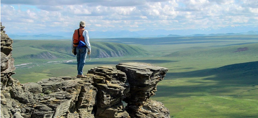 A geologist with the U.S. Geological Survey on an outcrop of Nanushuk Formation, Tuktu Bluff, Alaska.