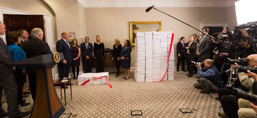 """President Trump prepares to cut the """"red tape"""" of regulations during a photo op at the White House on Dec. 14, 2017."""