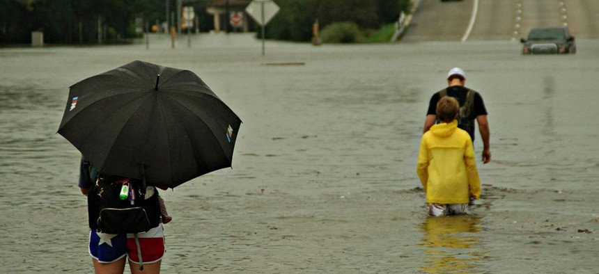 A woman and child watch as family returns to their stranded vehicle in Houston on Aug. 27, 2017.