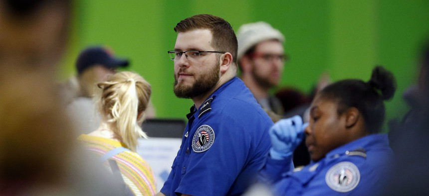 TSA officers work without pay at a checkpoint at Logan International Airport in Boston during the partial government shutdown on Jan. 5.