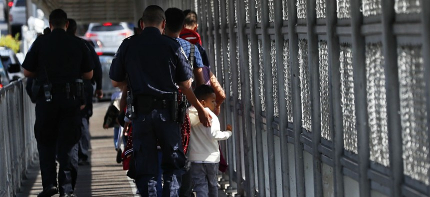 Customs and Border Protection officers escort migrants being taken to apply for asylum in the United States, on the International Bridge 1 in Nuevo Laredo, Mexico.
