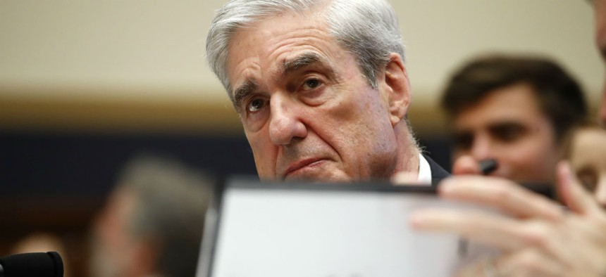 Former special counsel Robert Mueller, checks pages in the report as he testifies before the House Judiciary Committee hearing on his report on Russian election interference on Wednesday