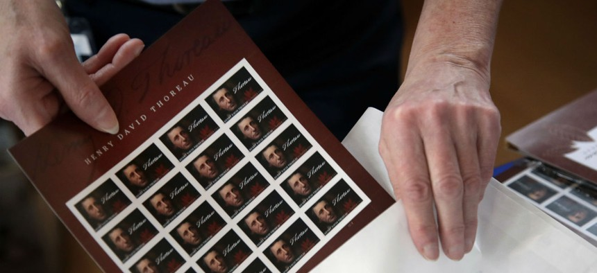 In May 2017, U.S. Postal Service worker Dianne Zambelli places a sleeve of newly dedicated Henry David Thoreau postage stamps for purchase in a bag in Concord, Mass.