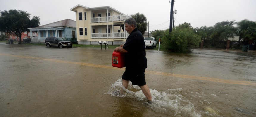 Angel Marshman carries a gas can as he walks through floodwaters from Tropical Depression Imelda to get to his flooded car, Wednesday, Sept. 18, 2019, in Galveston, Texas.
