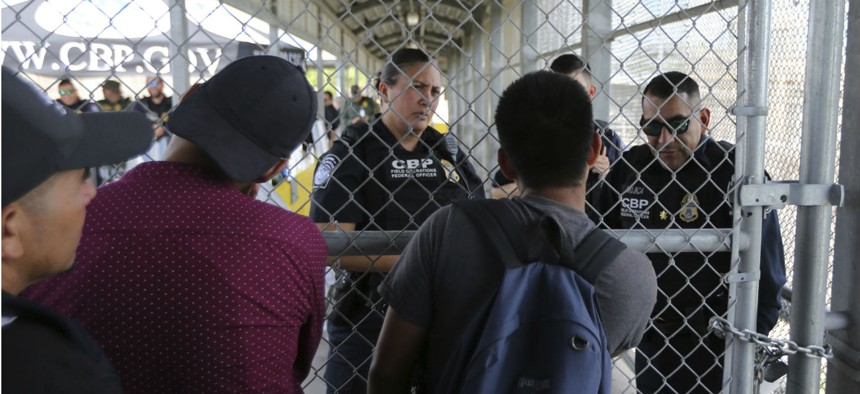 Migrants planning to seek asylum ask Customs and Border Protection officers when the border will re-open, after camping out on the Gateway International Bridge that connects downtown Matamoros, Mexico with Brownsville, Texas.